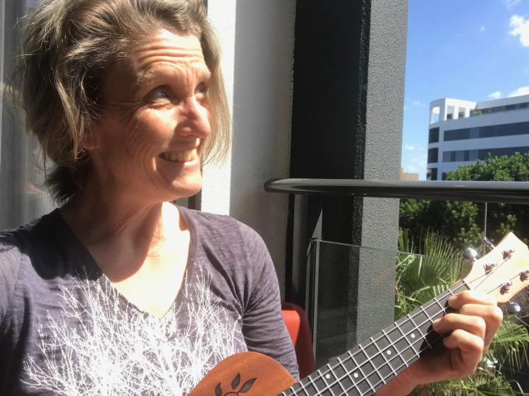 woman playing ukulele on balcony